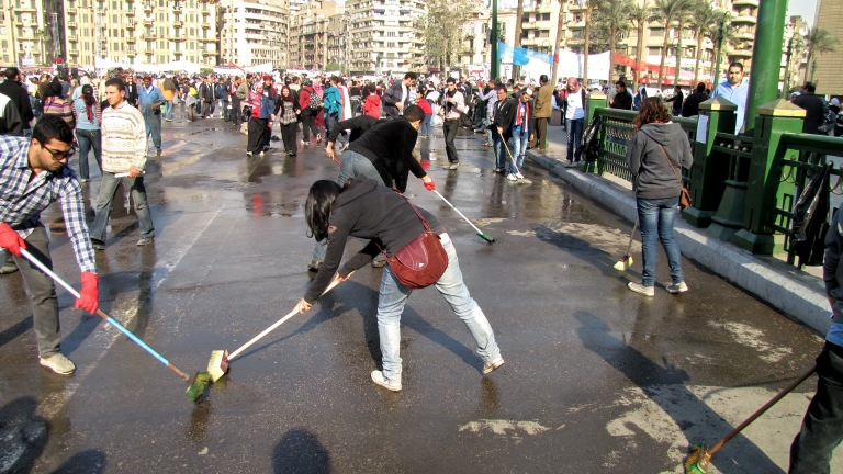 Protesters and volunteers sweep Tahrir Square, during the Egyptian Revolution of 2011, a day after Hosni Mubarak's resignation as president, in a gesture of a new beginning.